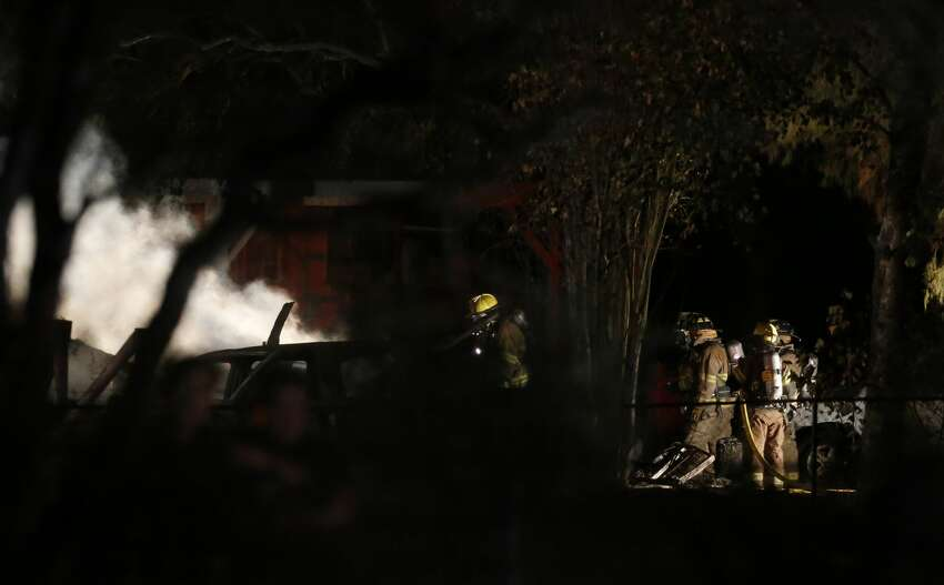 Bexar County Sheriff's Office and fire fighters respond to a structure fire in South Bexar County near Von Ormy on Wednesday, Nov. 15, 2017. Around 9 p.m. neighbors heard screaming and signs of a fire. Initial reports indicated that people were trapped in the structure. As of 10:41 p.m. fire fighters were still on the scene. (Kin Man Hui/San Antonio Express-News)