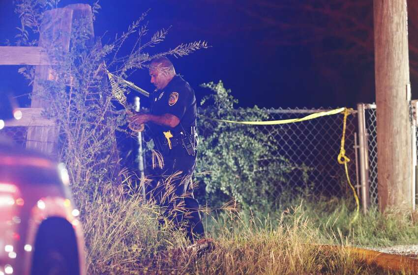 Bexar County Sheriff's Office deputy puts up crime scene tape as fire fighters respond to a structure fire in South Bexar County near Von Ormy on Wednesday, Nov. 15, 2017. Around 9 p.m. neighbors heard screaming and signs of a fire. Initial reports indicated that people were trapped in the structure. As of 10:41 p.m. fire fighters were still on the scene. (Kin Man Hui/San Antonio Express-News)