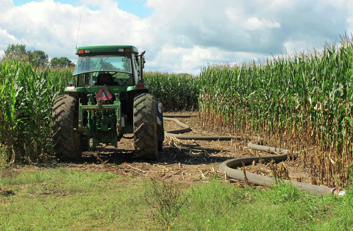 ADVANCE FOR USE THURSDAY, NOV. 16, 2017 AND THEREAFTER-This Sept. 14, 2016 photo shows a tractor and a hose used to spread manure on a cornfield in Kewaunee County, Wis., where nutrient runoff has polluted surface waters and drinking water wells. Chemicals and manure intended to nourish crops are washing into lakes, streams and oceans, providing an endless buffet for algae. (AP Photo/John Flesher) ORG XMIT: NY405