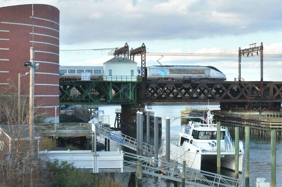 The aquarium research vessel, R/V Spirit of the Sound sits docked next to the IMAX theater at The Maritime Aquarium while an Amtrack Acela train passes over the Walk Bridge spanning the Norwalk river in the background on Wednesday November 15, 2017 in Norwalk Conn. Photo: Alex Von Kleydorff / Hearst Connecticut Media / Norwalk Hour
