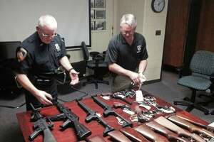 Stamford police officer Joseph Steyer, left, and Sgt. Tom Wolff holding three of the 48 guns turned over by the public during the department's buyback events in 2014.