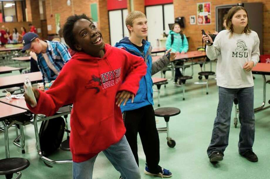 Tanner Bowerson, 16, center, and Bryson Bennett, 11, right, play Just Dance 2 on the Wii during The ROCK, a daily after-school program featuring snacks, tutors, crafts and games, on Wednesday at Jefferson Middle School. The ROCK is a non-profit that provides developmental education, after school programs, and community-based activities for middle and high school students at various locations in the greater Midland area. (Katy Kildee/kkildee@mdn.net)