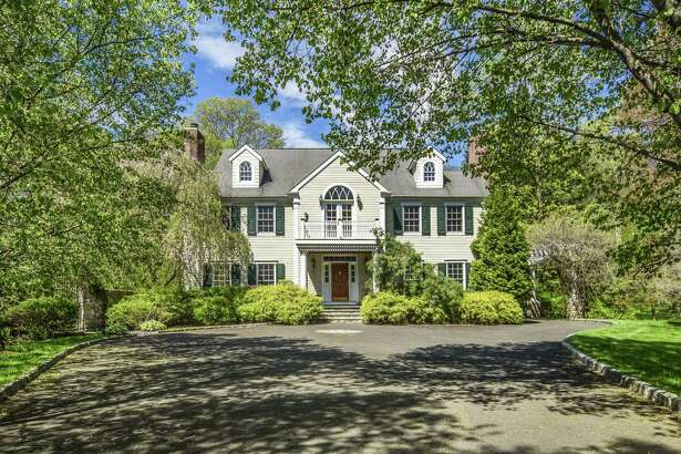 The 17-room colonial house at 98 Indian Waters Drive features a port cochere draped in wisteria vines and an attached guest house.