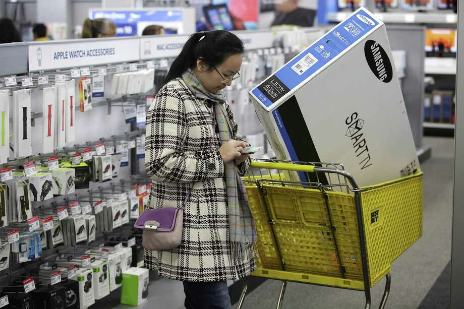 A customer uses her mobile phone as she shops in November 2015 in Skokie, Ill. In advance of the 2017 Black Friday holiday shopping promotion after Thanksgiving, the San Francisco-based cybersecurity analysis firm RiskIQ is warning that one in 25 apps created with a Black Friday theme are malicious with the intent of misappropriating personal information or other bad acts. Photo: Joshua Lott / Getty Images / 2015 Getty Images