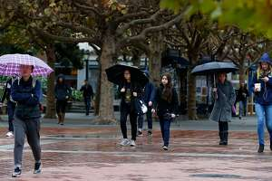 Students walk through Sproul Plaza during light rain at UC Berkeley on Wednesday, Nov. 15, 2017. The skies forecast to open up with a heavier downpour later this evening.