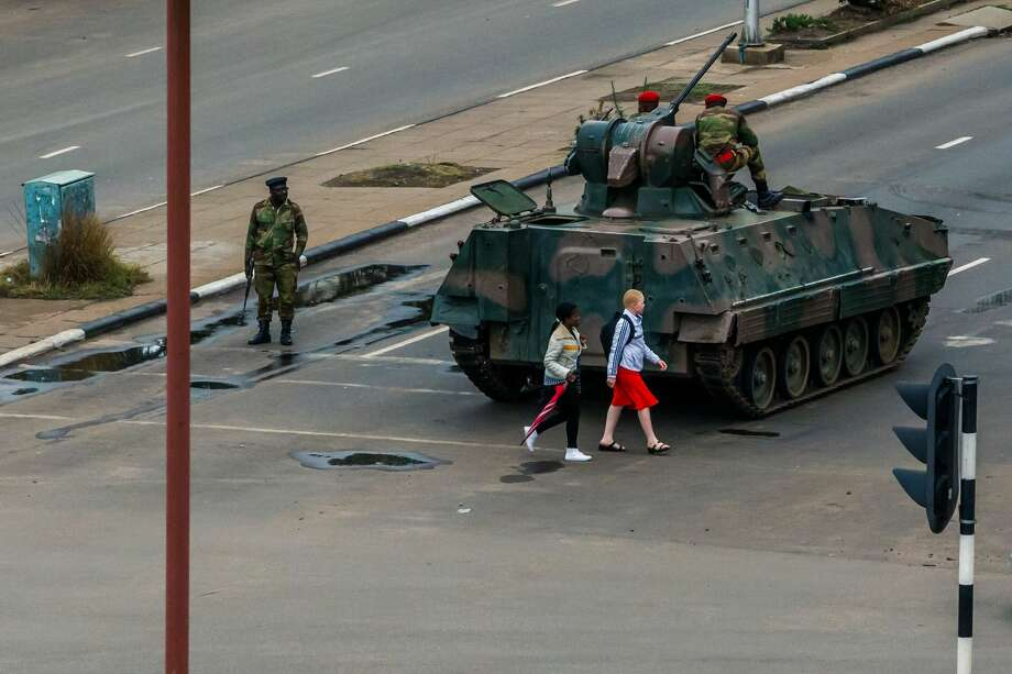 """Young women walk past an armoured personnel carrier that stations by an intersection as Zimbabwean soldiers regulate traffic in Harare on November 15, 2017. Zimbabwe's military appeared to be in control of the country on November 15 as generals denied staging a coup but used state television to vow to target """"criminals"""" close to President Mugabe. Photo: -/AFP/Getty Images"""
