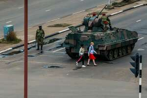 """TOPSHOT - Young women walk past an armoured personnel carrier that stations by an intersection as Zimbabwean soldiers regulate traffic in Harare on November 15, 2017. Zimbabwe's military appeared to be in control of the country on November 15 as generals denied staging a coup but used state television to vow to target """"criminals"""" close to President Mugabe."""