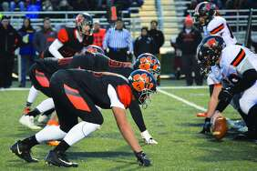 The Edwardsville defensive line sets up for a play during the second quarter of a quarterfinal game against Minooka inside the District 7 Sports Complex.