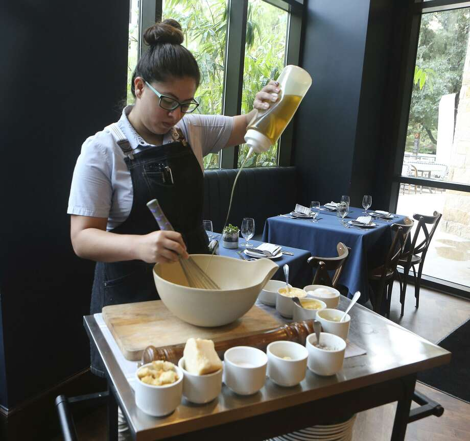 Raquel Contero adds olive oil to dressing for the tableside Caesar salad for two at Range restaurant on East Houston Street. Photo: John Davenport /San Antonio Express-News / ©John Davenport/San Antonio Express-News