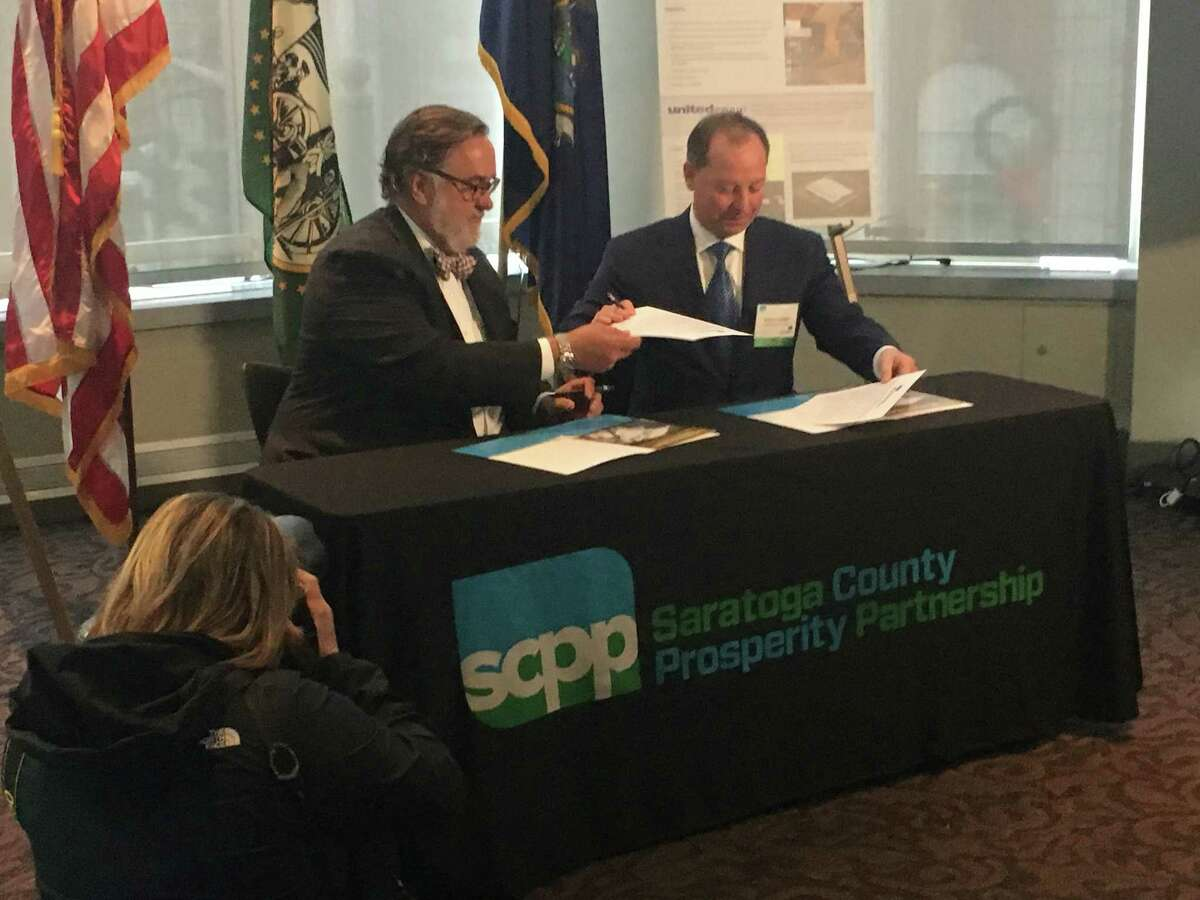 Marty Vanags, left, of the Saratoga County Prosperity Partnership, signs an agreement for space for Next Wave Center tenants with Michael Uccellini of the United Group of Cos. The center will host short-term space at United Group's building at 107 Hermes in the Saratoga Technology + Energy Park in Malta.