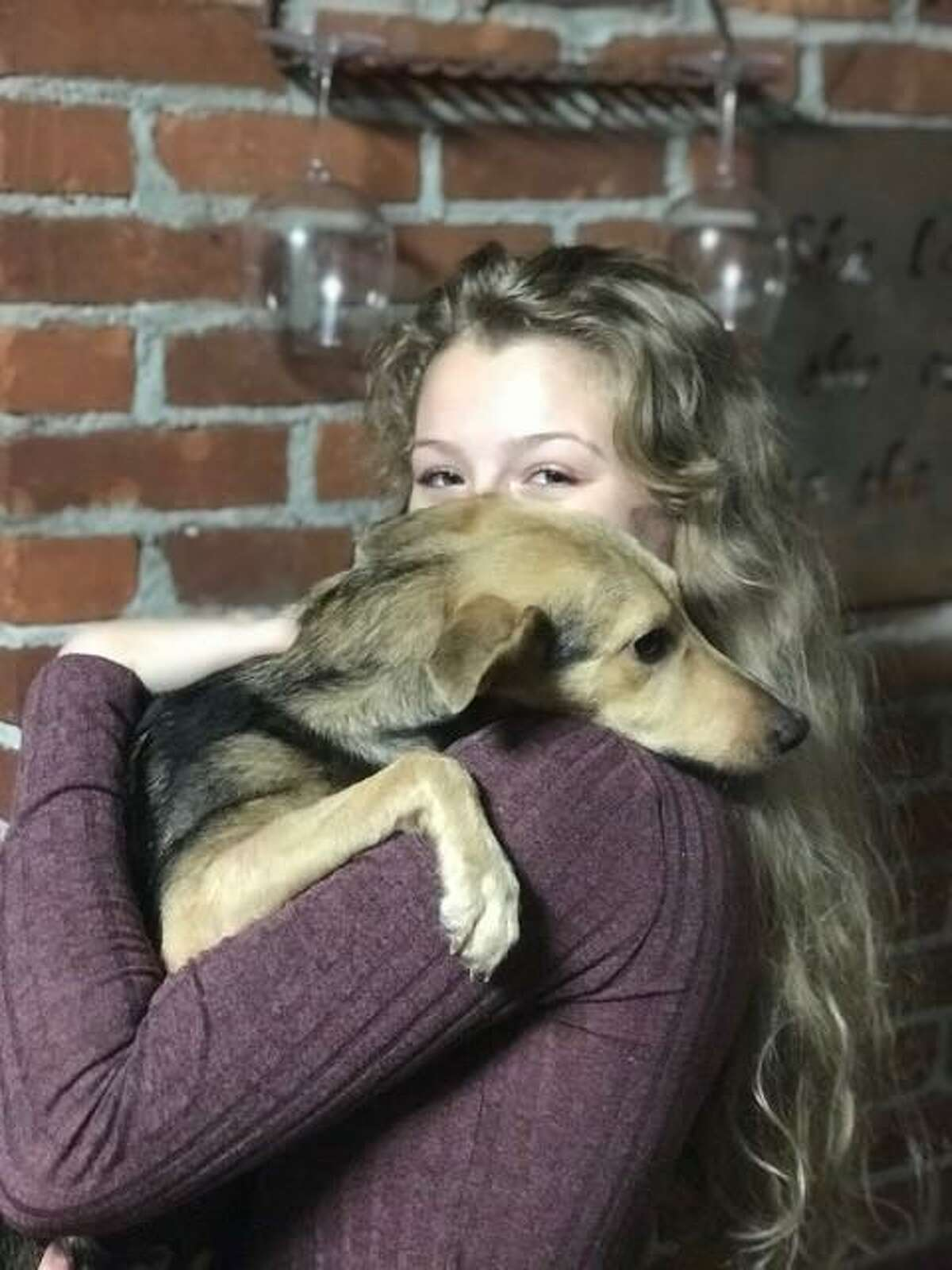 Gretta Silsdorf, 16, Kaeley Blum's oldest daughter holding Bubbles. After a tough trip, Bubbles has found a permanent home with the Blum family.