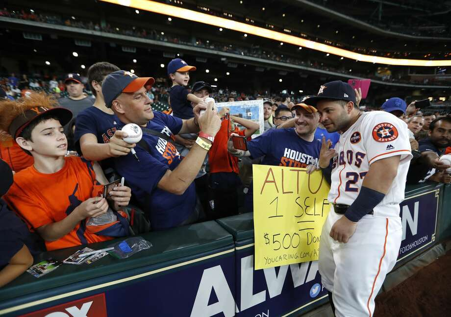 Houston Astros second baseman Jose Altuve (27) takes a selfie with fans who claim they would donate $500 to the Share To Care campaign before the start of an MLB baseball game at Minute Maid Park, Saturday, Sept. 2, 2017, in Houston.  This is the first professional sporting event in the city since Tropical Storm Harvey. Photo: Karen Warren/Houston Chronicle