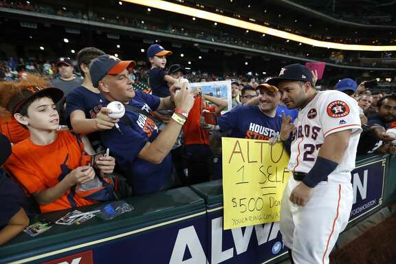 Houston Astros second baseman Jose Altuve (27) takes a selfie with fans who claim they would donate $500 to the Share To Care campaign before the start of an MLB baseball game at Minute Maid Park, Saturday, Sept. 2, 2017, in Houston.  This is the first professional sporting event in the city since Tropical Storm Harvey.