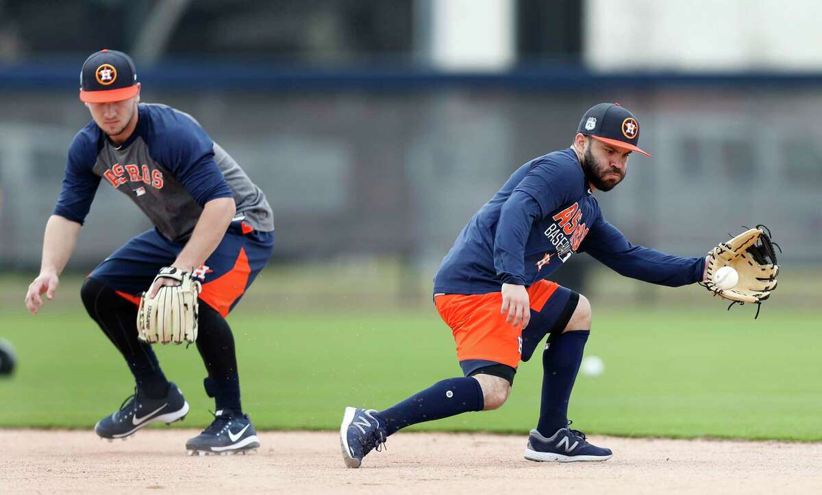 Houston Astros second baseman Jose Altuve reaches out to catch a ground ball as Alex Bregman watches as they worked out with the other position players who came to camp early during spring training at The Ballpark of the Palm Beaches, in West Palm Beach, Florida, Thursday, February 16, 2017.