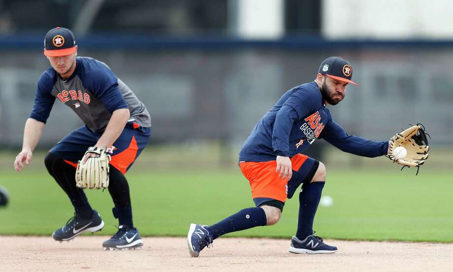 Houston Astros second baseman Jose Altuve reaches out to catch a ground ball as Alex Bregman watches as they worked out with the other position players who came to camp early during spring training at The Ballpark of the Palm Beaches, in West Palm Beach, Florida, Thursday, February 16, 2017. Photo: Karen Warren, Houston Chronicle / 2017 Houston Chronicle