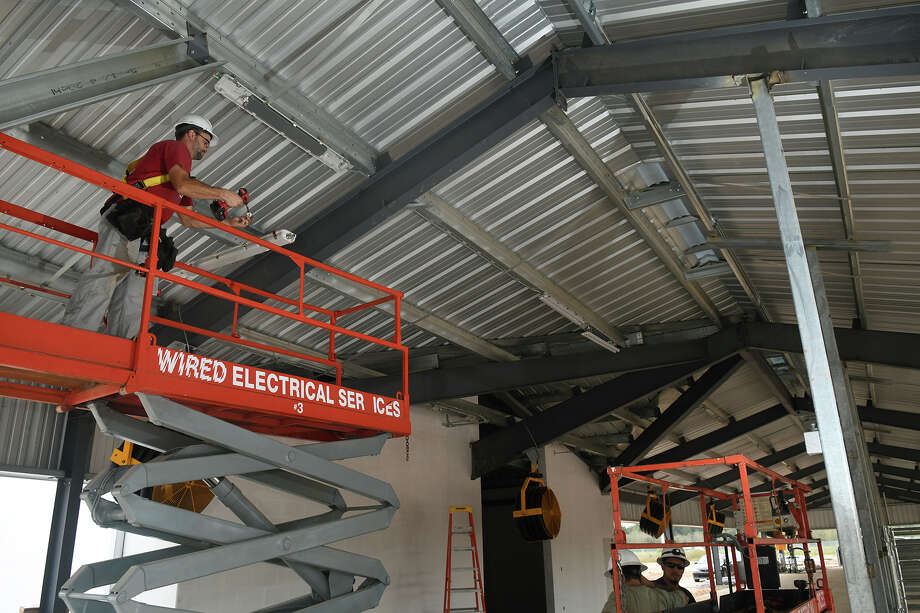 Renato Dubois, left, of Wired Electrical Services in Houston, installs a light fixture at new 14,770-square-foot Klein ISD Ag Barn, Northcrest Ag Facility, located across the street from Klein Oak High School, on Nov. 15, 2017. (Photo by Jerry Baker/Freelance) Photo: Jerry Baker, Freelance / Freelance