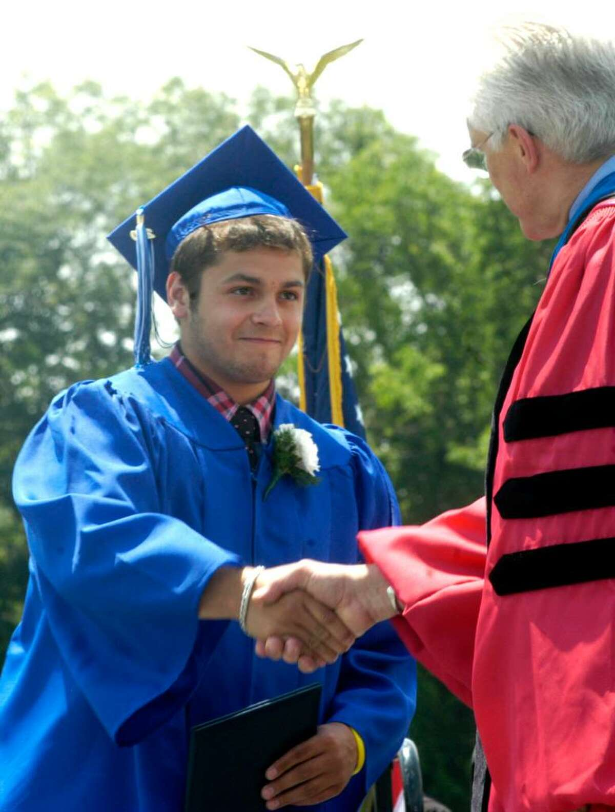 Alessandro Criollo receives a congratulatory handshake from Region 12 Superintendent of Schools Dr. Bruce Storm after accepting his diploma during Saturday's Shepaug Valley High School graduation on the school's rustic campus in Washington. June 26, 2010