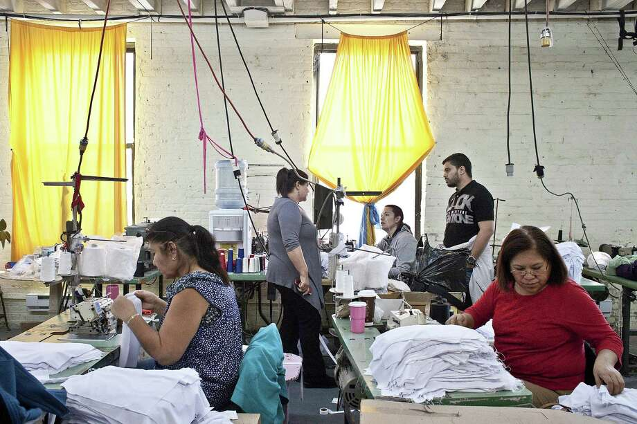 Workers sew dresses at CC Fashions in Union City, N.J., in 2016. Large companies defined by law as those with 50 or more workers are required to offer their employees affordable insurance or pay stiff tax penalties, a provision of the Affordable Care Act that the IRS will soon begin enforcing. Photo: Bryan Anselm /New York Times / NYTNS