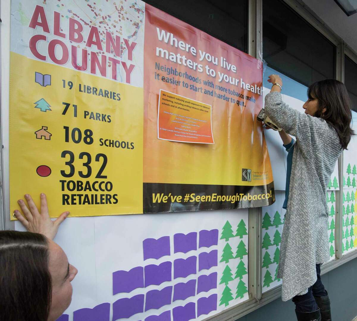 Jeanie Orr, right and Cara Zampi of the Capital District Tobacco-Free Communities put up an interactive map that reveals the problem of tobacco marketing in great capital district on the front of the Boys and Girls Club Thursday Nov. 16, 2017 in Albany, N.Y. (Skip Dickstein/ Times Union)