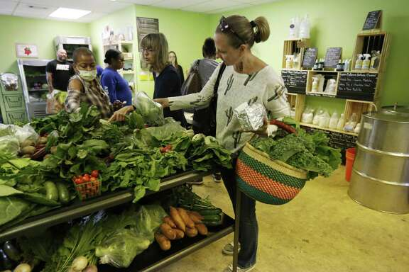 Consumer Olga Yashkova (right) sorts through a table of fresh vegetables at The Farm Connection, a member-based private grocery store owned by Beth Parks.