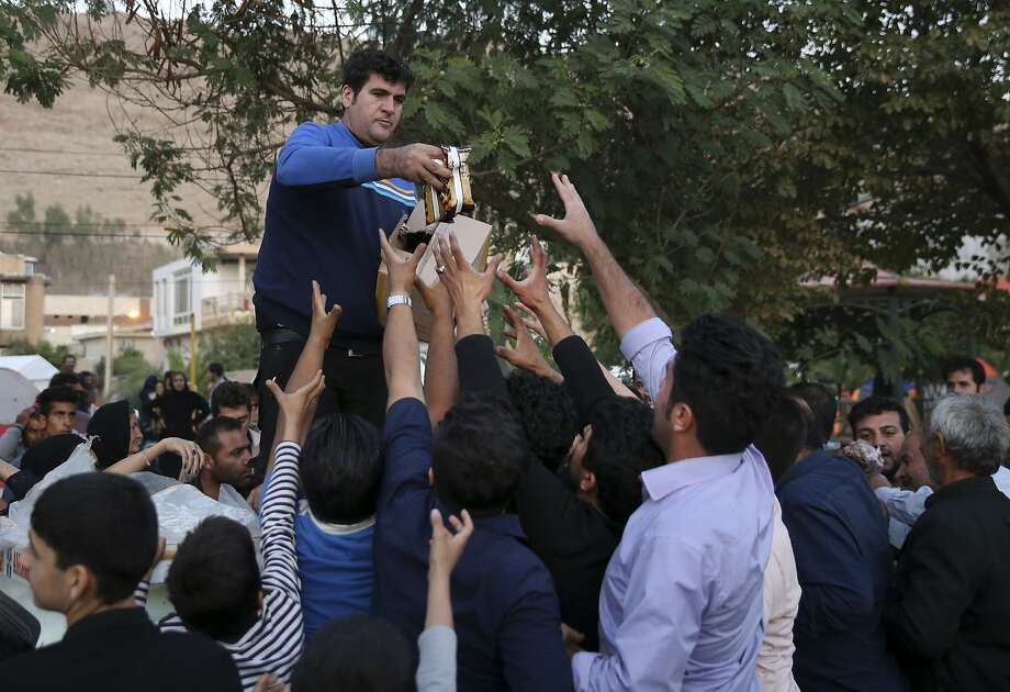 Sanctions bar Iranian-Americans from sending cash to help survivors, seen here receiving aid. Photo: Vahid Salemi, Associated Press