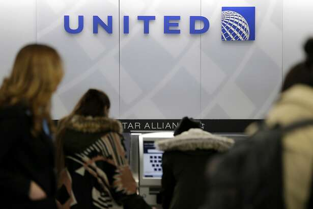 In this Wednesday, March 15, 2017, photo, people stand in line at a United Airlines counter at LaGuardia Airport in New York. In a report being issued Thursday, April 27, 2017, about the April 9 dragging incident involving a passenger on an overcrowded United Express plane, United spelled out how it selects passengers for involuntary bumping. (AP Photo/Seth Wenig)