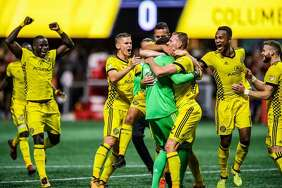 Columbus Crew players celebrate the game-winning goal after an MLS playoff game against Atlanta United, in Atlanta on Oct. 26, 2017. The Columbus Crew won in a 3-1 shootout.