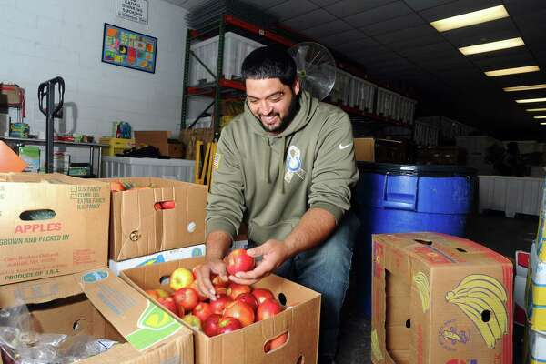 Frankie Molina, of Bridgeport, checks the expiration dates on fruits and vegetables as he unloads donations inside The Food Bank of Lower Fairfield County on Glenbrook Road in Stamford, Conn. on Thursday, Nov. 16, 2017.
