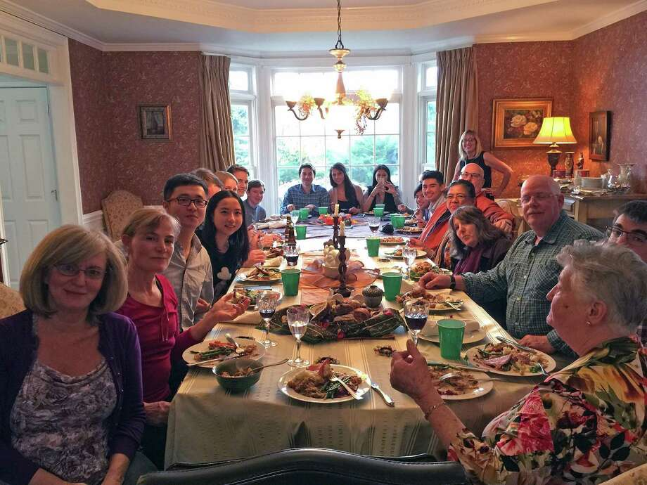 Pat Smith stands surrounded by her many Thanksgiving guests, including international students she hosted as part of the United Nations Association of Southwestern Connecticut in 2015. Photo: Contributed Photo