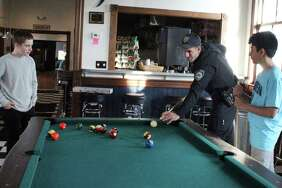 Officer Joe Cusano plays pool with students as part of the Darien Depot's Cops and Kids program.