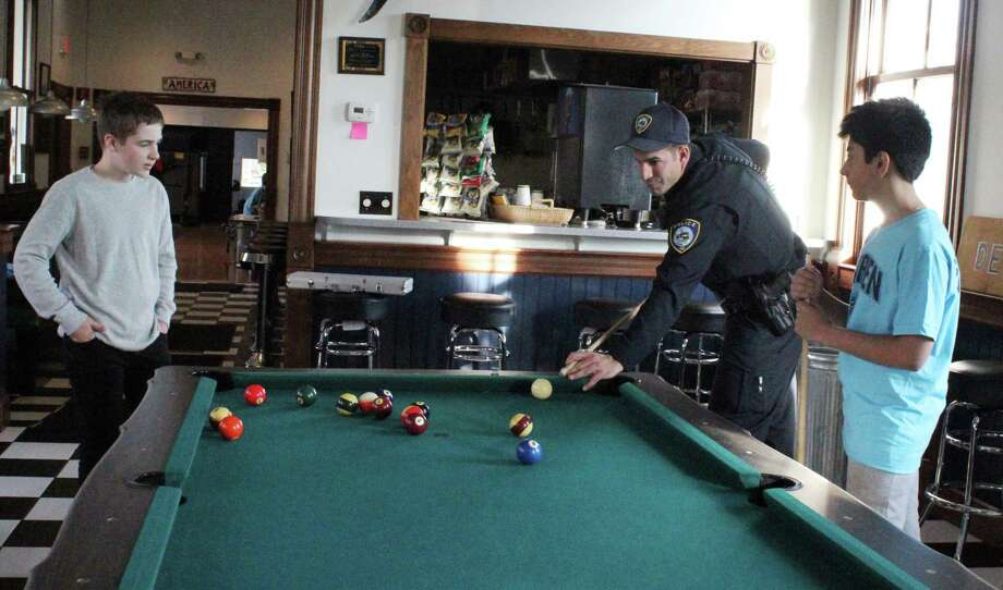 Officer Joe Cusano plays pool with students as part of the Darien Depot's Cops and Kids program. Photo: Erin Kayata / Hearst Connecticut Media / Darien News