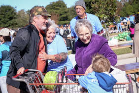Chuck Miller and his son Joseph, 3, are greeted by Gail Box, left, and Pam Bishop, right, during the annual Thanksgiving Grocery Giveaway on Saturday, Nov. 19, 2016, at The Ark Church in Conroe.