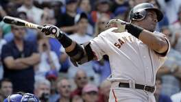 San Francisco Giants' Barry Bonds hits a three-run home run during the seventh inning of a baseball game in 2007 against the Chicago Cubs in Chicago. The cloud of steroids use will mar Bonds' achievements.