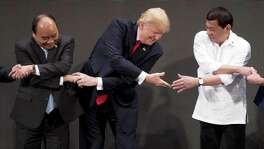 """President Donald Trump, center, reacts as he does the """"ASEAN-way handshake"""" with Vietnamese Prime Minister Nguyen Xuan Phuc, left, and Philippine President Rodrigo Duterte on stage during the opening ceremony at the ASEAN Summit at the Cultural Center of the Philippines Monday."""