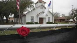 A rose is left in the fence surrounding the First Baptist Church of Sutherland Springs on Nov. 12. The congregation held its first service since the shooting that day in a tent in the towns ball park.