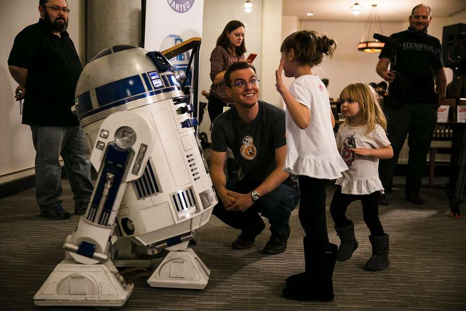 Six-year- old Emma Kelly shares her excitement with her father, Shawn Kelly, upon meeting R2-D2 at the Droid athon. Photo: Mason Trinca, Special To The Chronicle