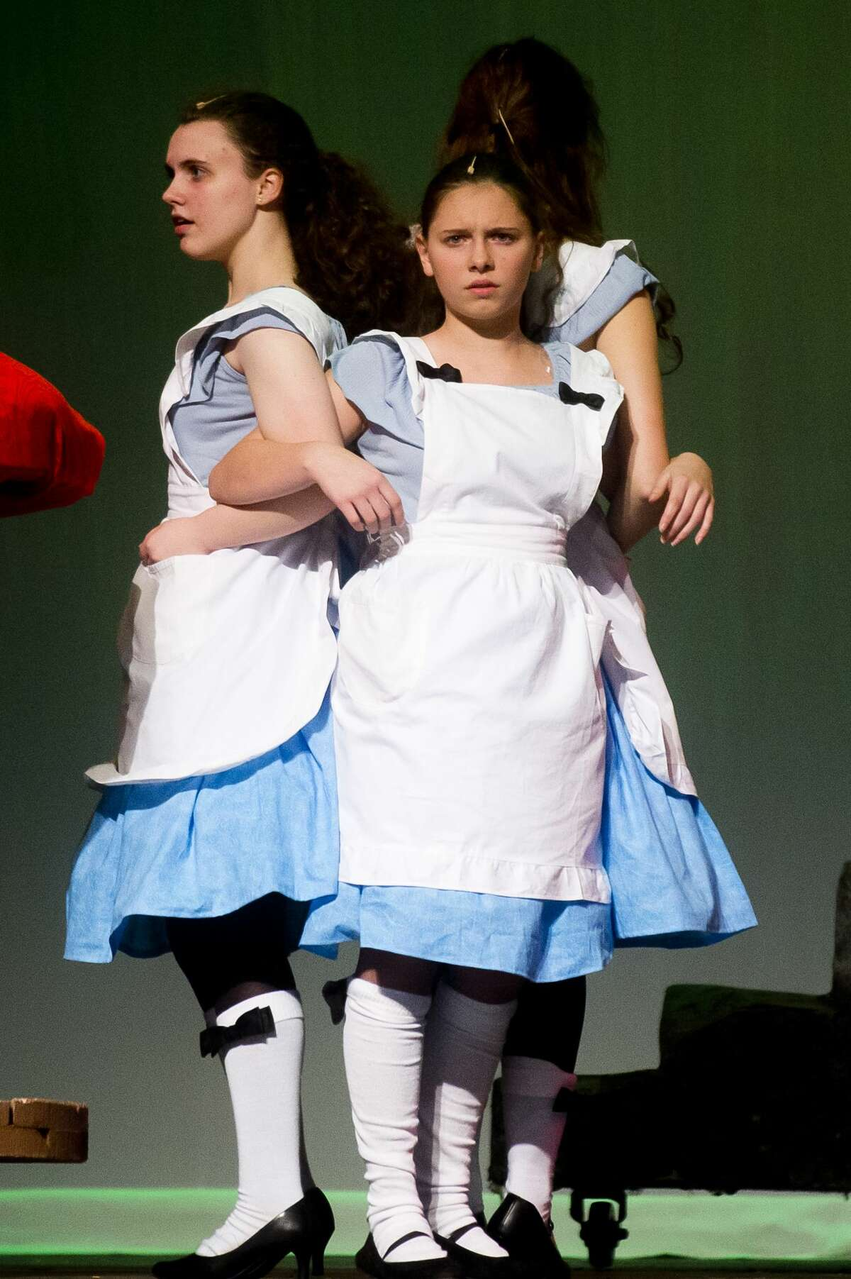 From left, Emma Allington, playing the role of Alice, Anna Stolz, playing the role of Small Alice, and Maggie Reed, playing the role of Tall Alice, act out a scene during a dress rehearsal on Wednesday, Nov. 15, 2017 for H. H. Dow High School's production of Adventures in Wonderland, which opened Thursday evening and continues at 7 p.m. Friday and Saturday, with a 3 p.m. Saturday matinee. (Katy Kildee/kkildee@mdn.net)