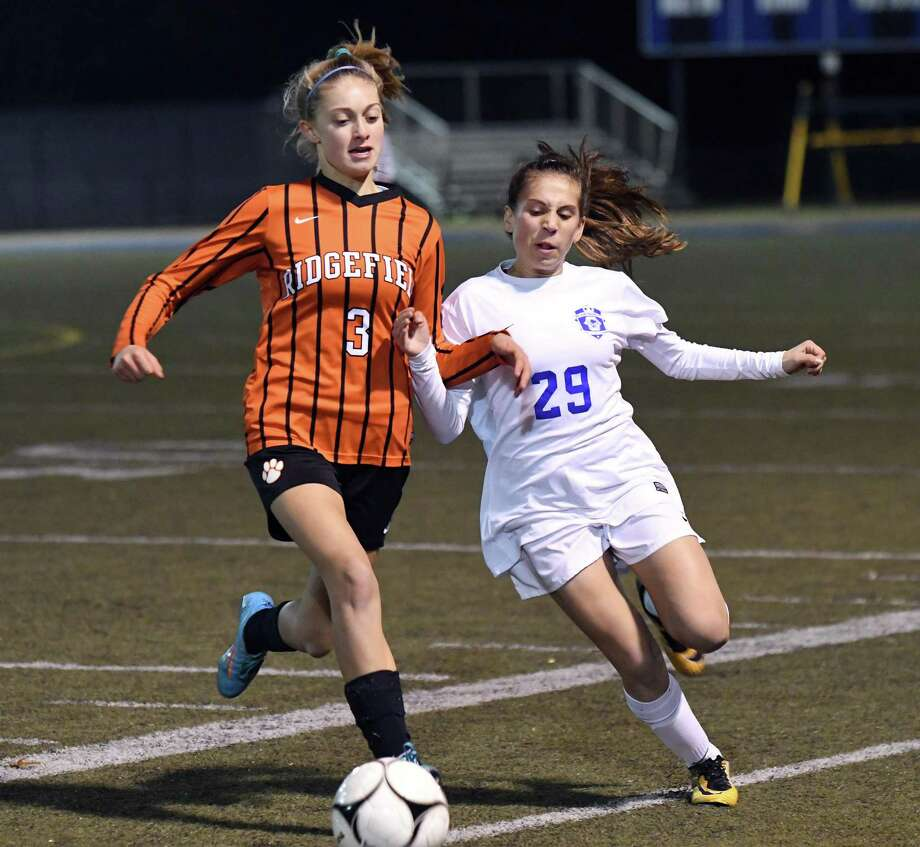 Ridgefield's Carolyn Donovan, left, vies for the ball with Glastonbury's Alexandra Bedard during the Class LL state girls soccer semifinal between Ridgefield and Glastonbury at Municipal Stadium in Waterbury 10/15/17. Photo: Krista Benson / The News-Times Freelance