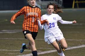Ridgefield's Carolyn Donovan, left, vies for the ball with Glastonbury's Alexandra Bedard during the Class LL state girls soccer semifinal between Ridgefield and Glastonbury at Municipal Stadium in Waterbury 10/15/17.