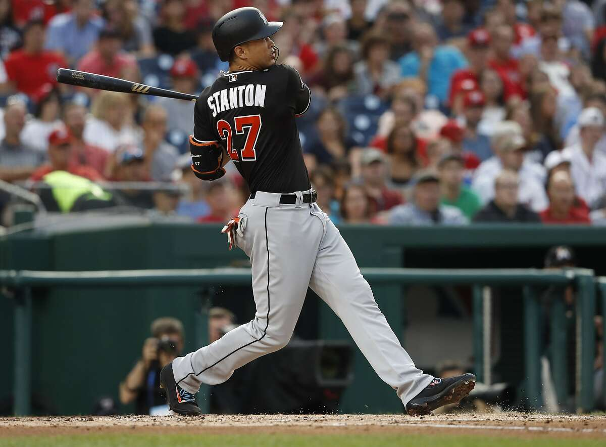 FILE - In this Aug. 10, 2017, file photo, Miami Marlins' Giancarlo Stanton (27) watches his two-run home run during the third inning of the team's baseball game against the Washington Nationals in Washington. Houston dynamo Jose Altuve and Yankees slugger Aaron Judge are the favorites for the AL MVP award while Miami masher is the top candidate for the NL prize. (AP Photo/Carolyn Kaster, File)