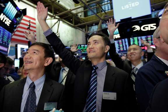 Jianpu Technology's co-founder & CEO Daqing Ye, center, waves to a gallery in the New York Stock Exchange as he waits for his company's IPO to begin trading, Thursday, Nov. 16, 2017. (AP Photo/Richard Drew)