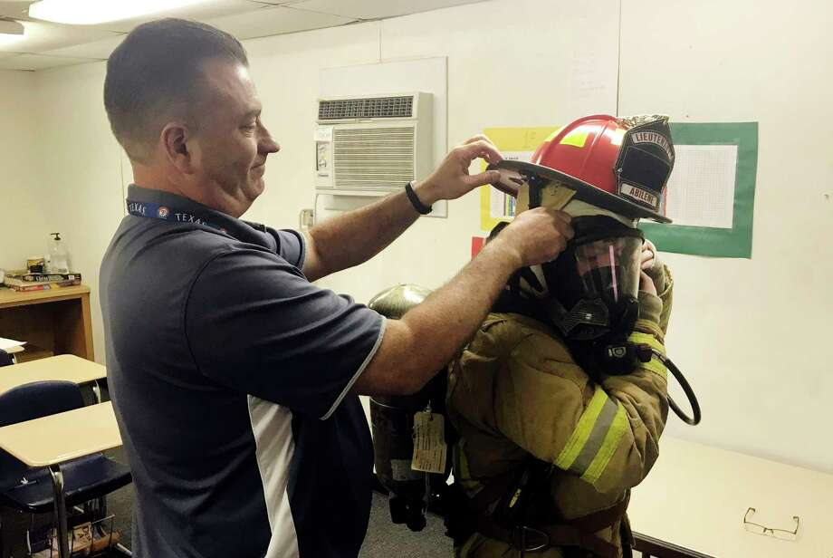 ADVANCE FOR MONDAY, NOV. 20 - In this Friday, Nov. 3, 2017 photo, Mike Miller, left, formerly a lieutenant in the Abilene Fire Department, helps Abilene High School sophomore Cameron Mitchell into firefighting bunker gear in Abilene, Texas. The firefighter training courses won't officially begin until next year, when Miller introduces the first two semesters of a planned four-semester program. (Timothy Chipp/The Abilene Reporter-News via AP) Photo: Timothy Chipp, AP / The Abilene Reporter-News