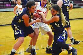 Father McGivney's Madison Webb, left, and Sierra Williams, right, tie up a Roxana player for a jump ball in the first quarter of Thursday's game in Dupo.