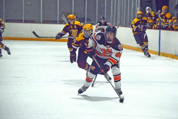 Edwardsville's Trevor Dailey, right, looks to pass the puck during Thursday's game against De Smet at the East Alton Ice Arena.