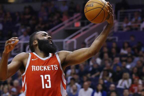 Houston Rockets guard James Harden (13) beats the Phoenix Suns defense, including guard Troy Daniels, right, to score during the first half of an NBA basketball game Thursday, Nov. 16, 2017, in Phoenix. (AP Photo/Ross D. Franklin)