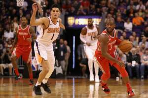 PHOENIX, AZ - NOVEMBER 16:  Chris Paul #3 of the Houston Rockets moves the ball past Devin Booker #1 of the Phoenix Suns during the first half of the NBA game at Talking Stick Resort Arena on November 16, 2017 in Phoenix, Arizona. NOTE TO USER: User expressly acknowledges and agrees that, by downloading and or using this photograph, User is consenting to the terms and conditions of the Getty Images License Agreement.  (Photo by Christian Petersen/Getty Images)