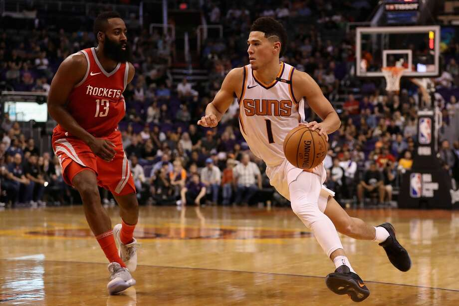 Suns guard Devin Booker is now playing the point because interim coach Jay Triano was inspired by James Harden's effectiveness after he switched to point guard. Photo: Christian Petersen/Getty Images
