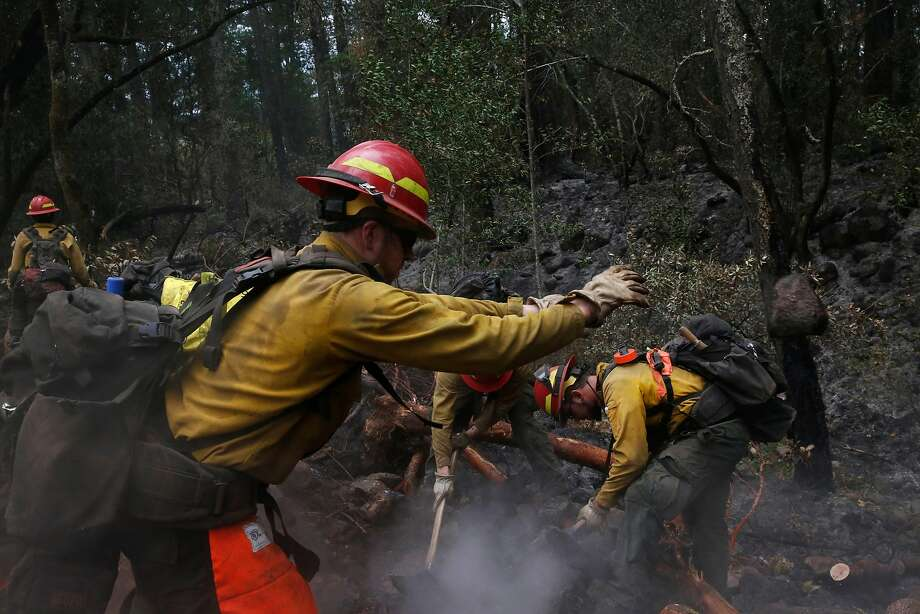 Eugene, Ore., firefighters Cameron McConnell (left), Skylar Lillingston and John Peterson work on the blaze last month near Sugarloaf Ridge State Park in the Sonoma County community of Kenwood. Photo: Leah Millis, The Chronicle