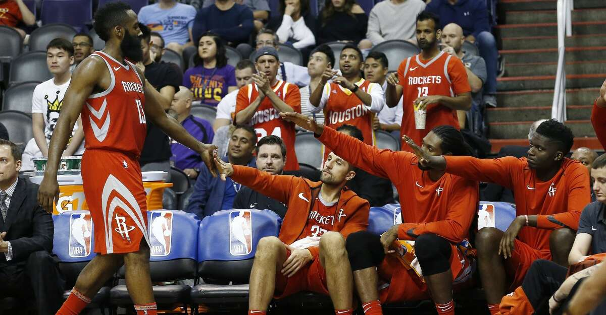 Houston Rockets guard James Harden (13) returns to the bench and a welcome from teammates Ryan Anderson, second from left, Nene Hilario, second from right, and Clint Capela, right, during the second half of an NBA basketball game against the Phoenix Suns on Thursday, Nov. 16, 2017, in Phoenix. The Rockets won 142-116. (AP Photo/Ross D. Franklin)