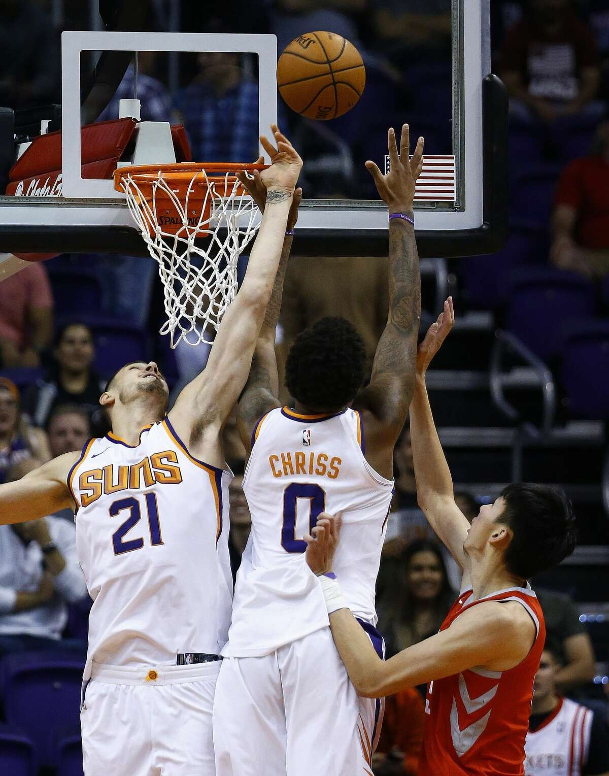 Phoenix Suns center Alex Len (21) and forward Marquese Chriss (0) block the shot of Houston Rockets forward Zhou Qi, right, of China, during the second half of an NBA basketball game Thursday, Nov. 16, 2017, in Phoenix. The Rockets defeated the Suns 142-116. (AP Photo/Ross D. Franklin)